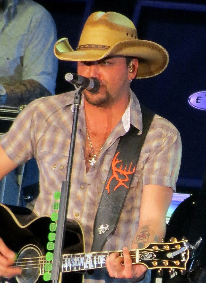 Jason Aldean playing guitar and singing songs during his performance