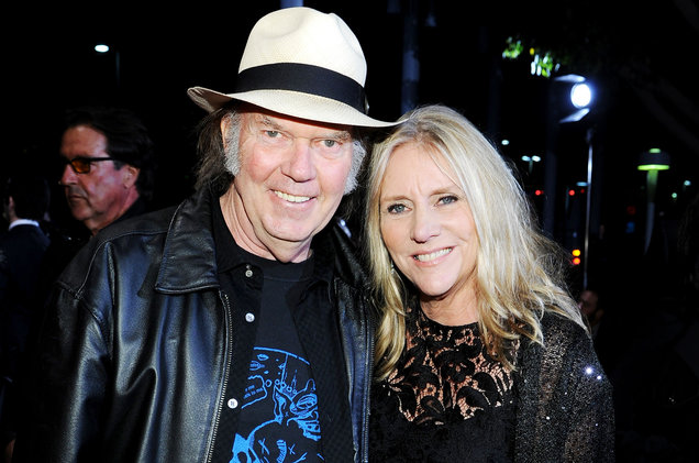 Musician duo, Neil Young and Pegi Young smiling while posing for a picture together