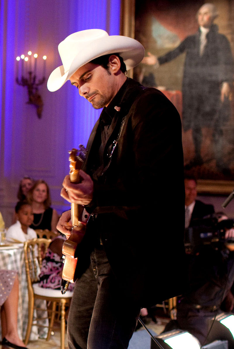 Brad Paisley performing for his audiences. He is wearing a hat and playing a guitar