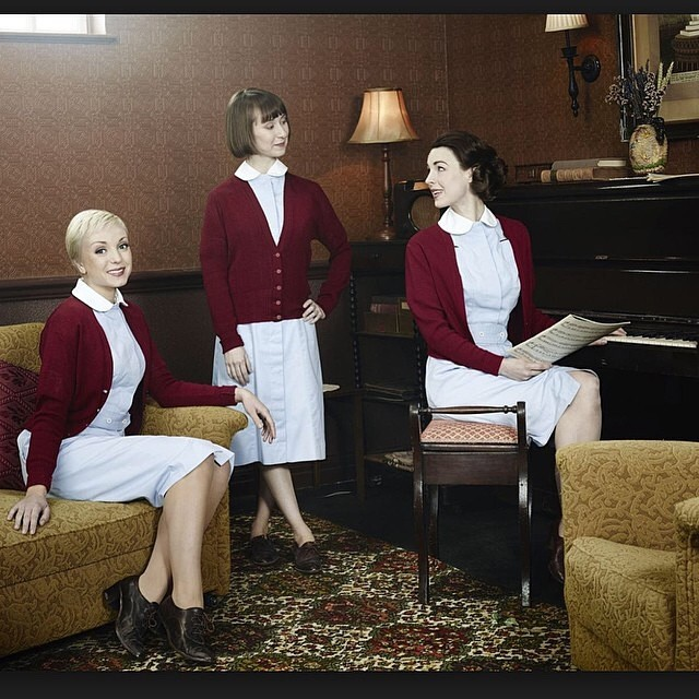 The three cast members of Call the Midwife, where is standing and the rest two are sitting on a chair and a couch