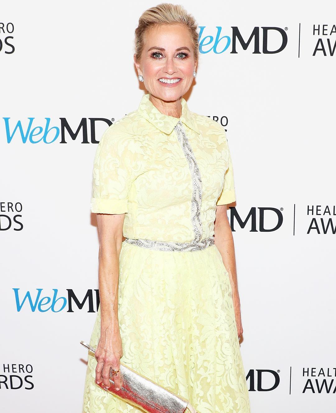 Maureen McCormick is wearing light yellow dress holding a purse on her hand