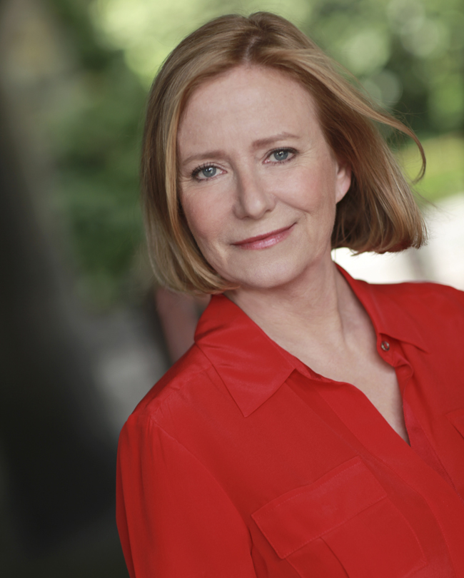 Eve Plumb is wearing a red shirt slaying her short hair look