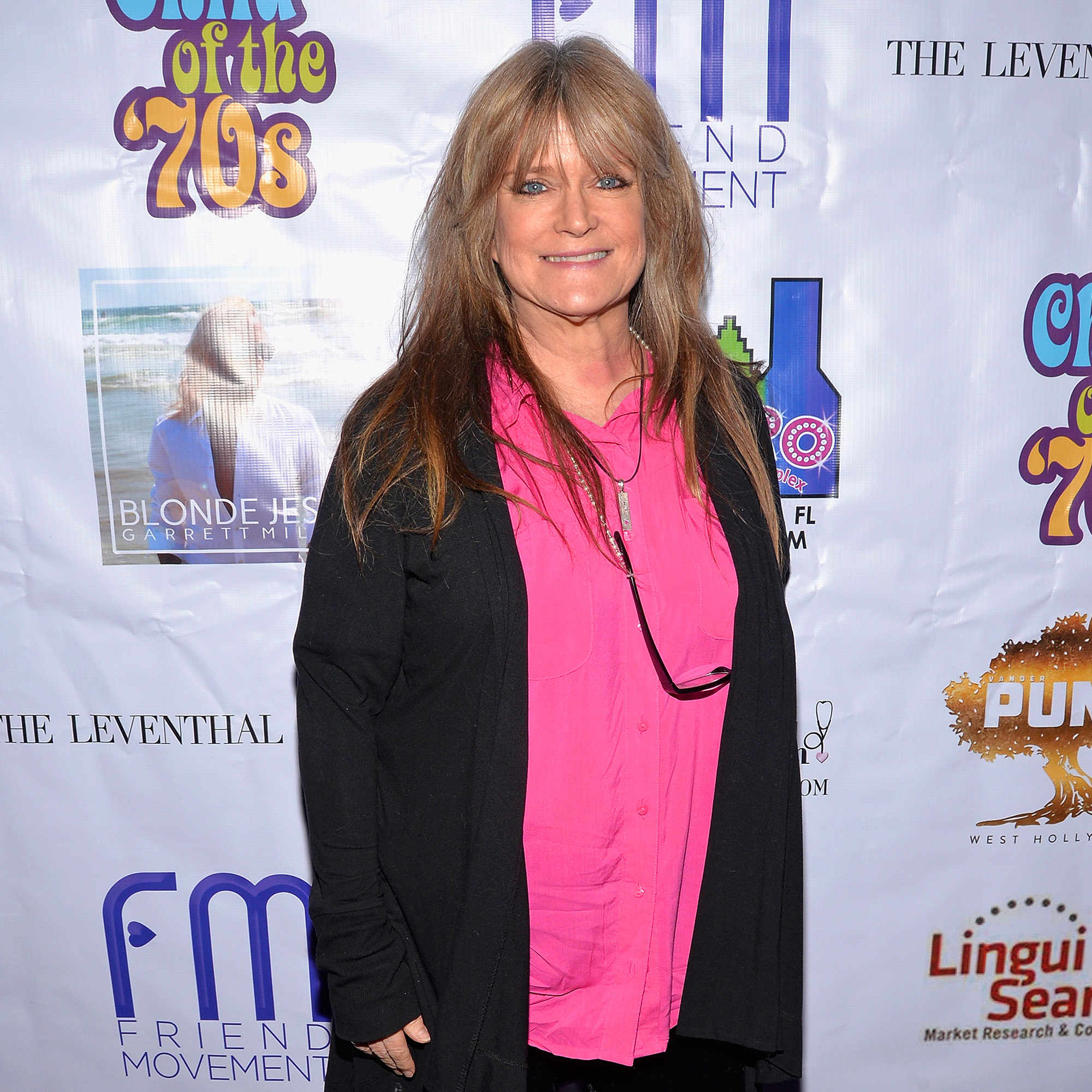 Susan Olsen attends an event in a pink colored dress and a black outer