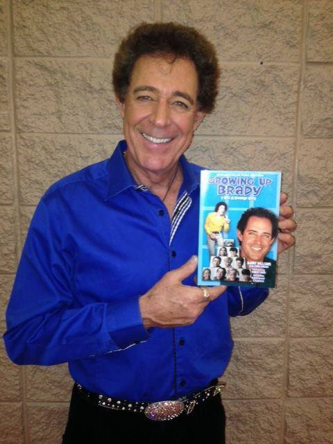 Barry Williams holding his autobiography, Growing Up Brady; I Was A Teenage Greg