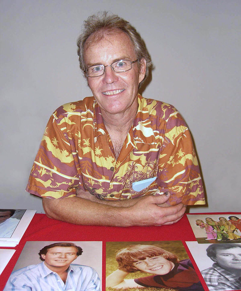 Mike Lookinland is wearing spectacles while leaning slightly on a table which consists of pictures of The Brady Bunch cast