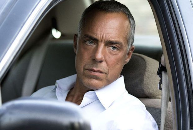 Titus Welliver is sitting in the front seat of a car wearing a white shirt