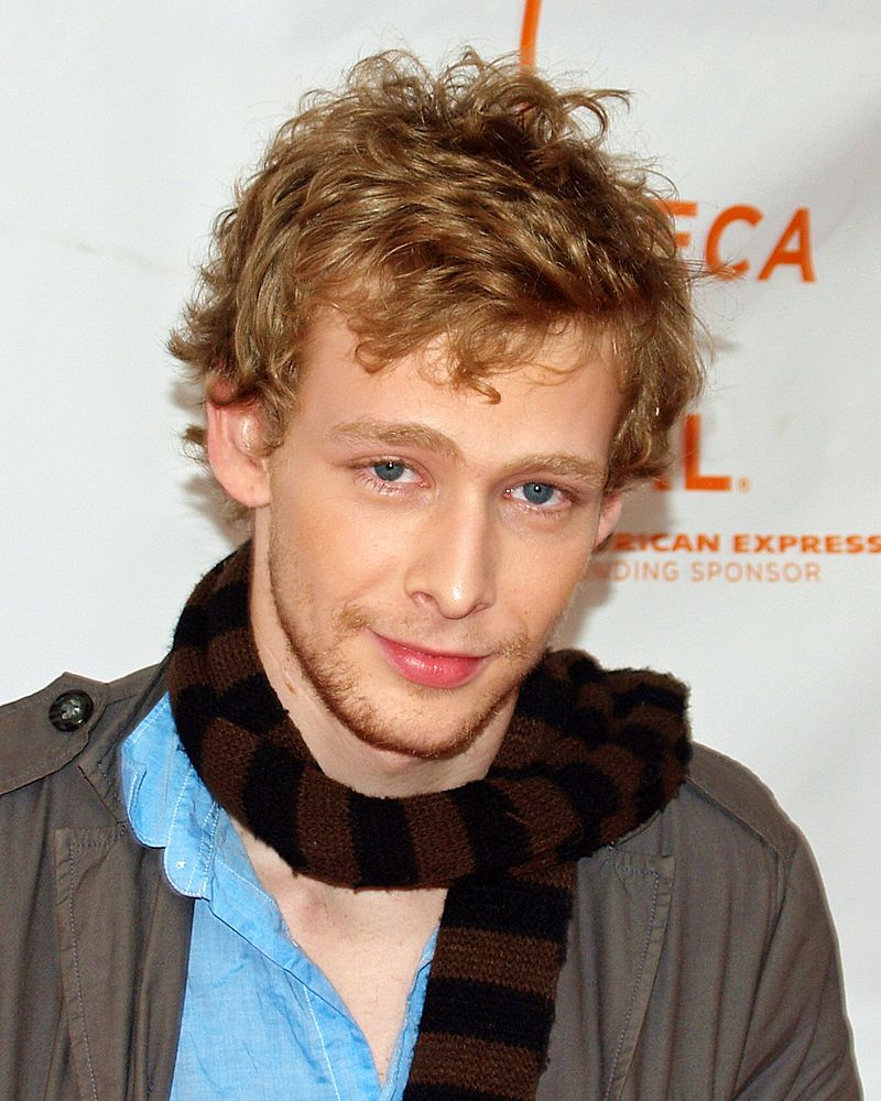 Johnny Lewis is wearing a woolen scarf around his neck with a subtle smile on his face