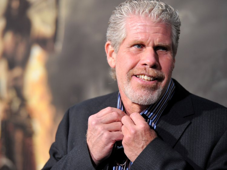 Ron Perlman is tying up his uppermost button of his shirt
