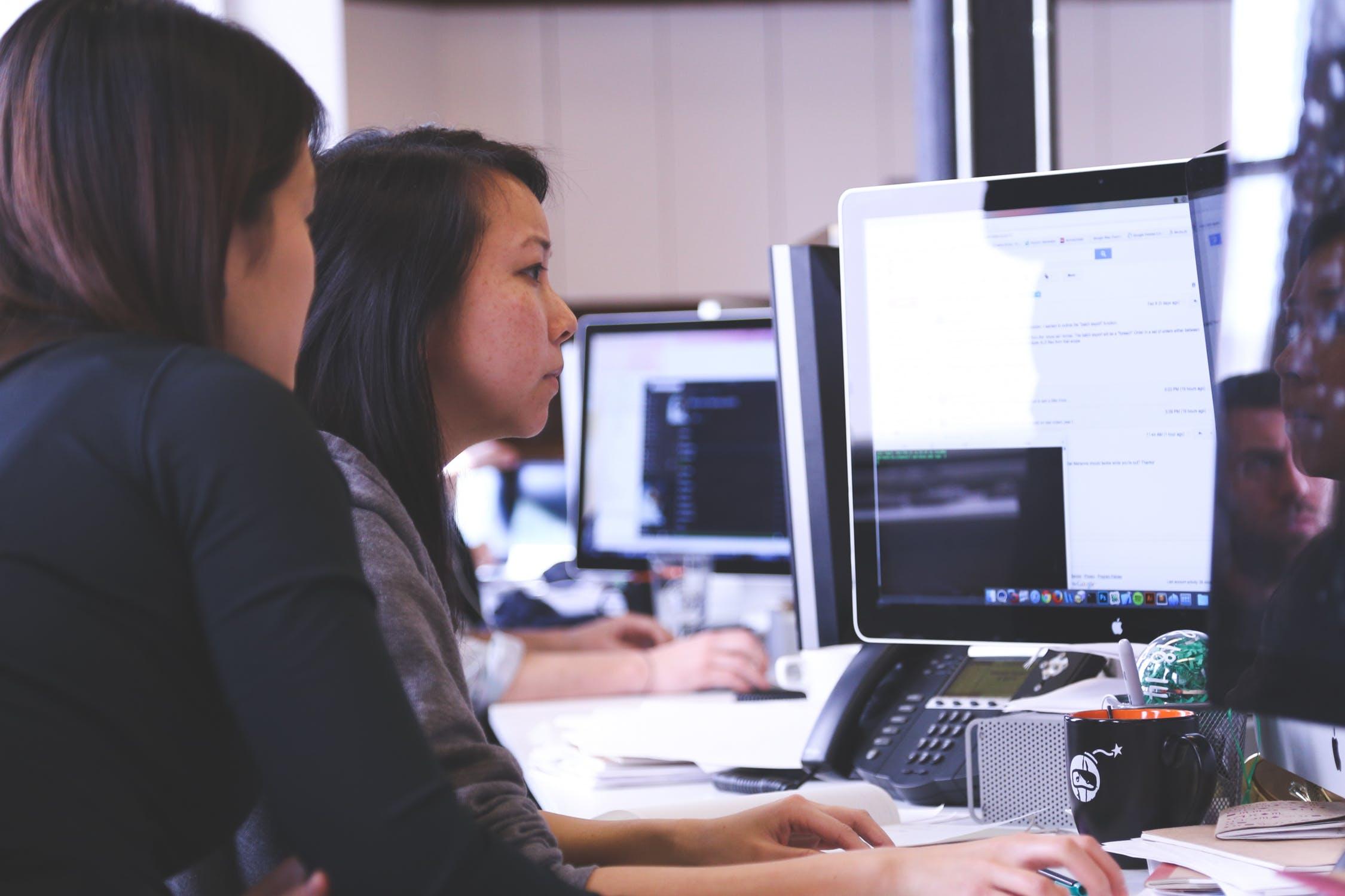 Two women looking a desktop.