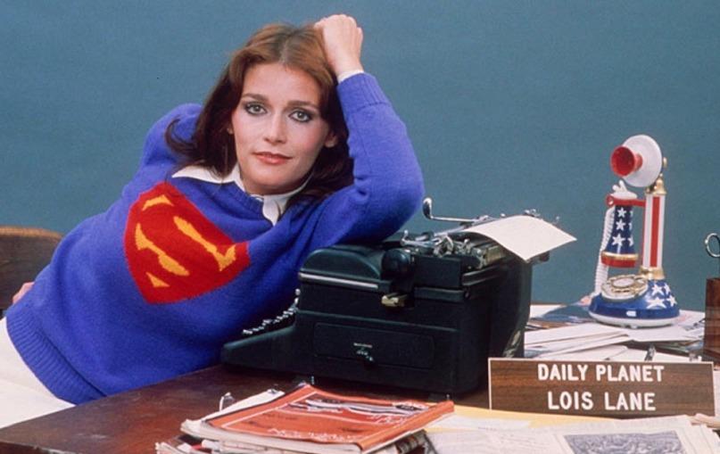 Margot Kidder posing for a photo wearing a blue superman sweater.