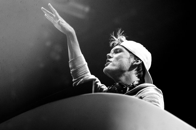 Black and white image of Avicii performing. He is wearing a white cap