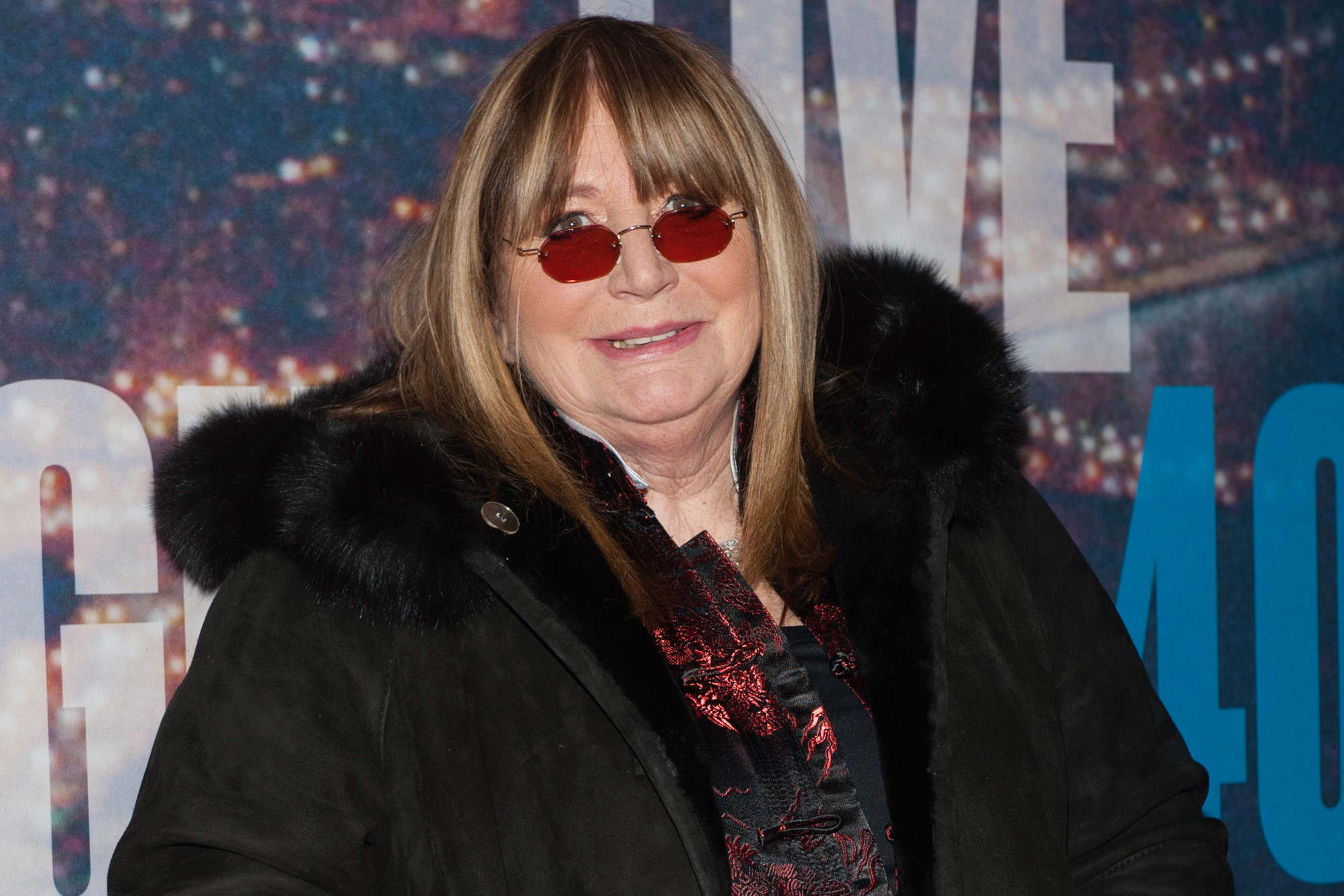 Penny Marshall smiling. She is wearing red specs