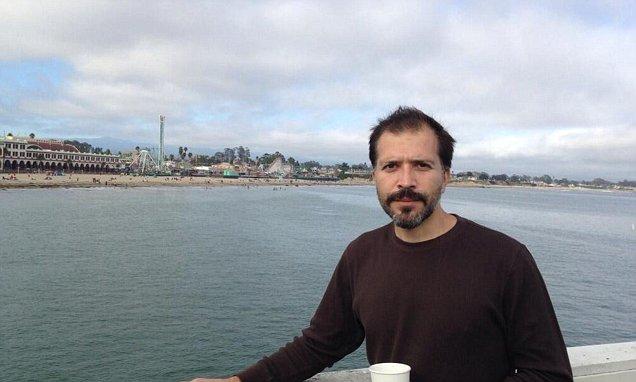 Paul John Vasquez posing for a photo wearing a sweat shirt. He is wearing a cup in her hand