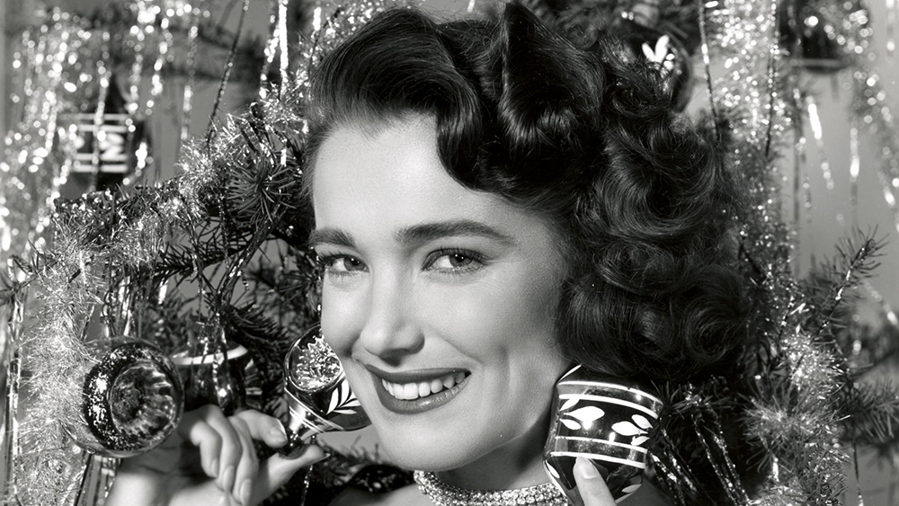 Julie Adams in front of a Christmas tree. She is smiling