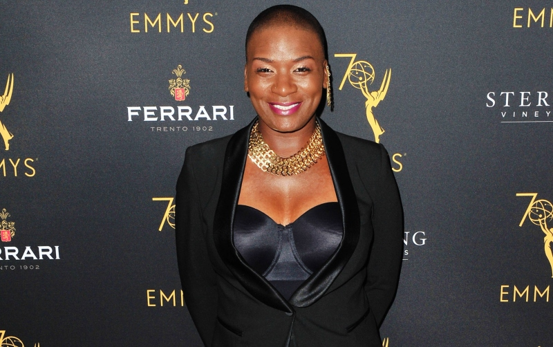 Janice Freeman smiling for a photo at the Emmy Awards. She is wearing a black suit and jewelry