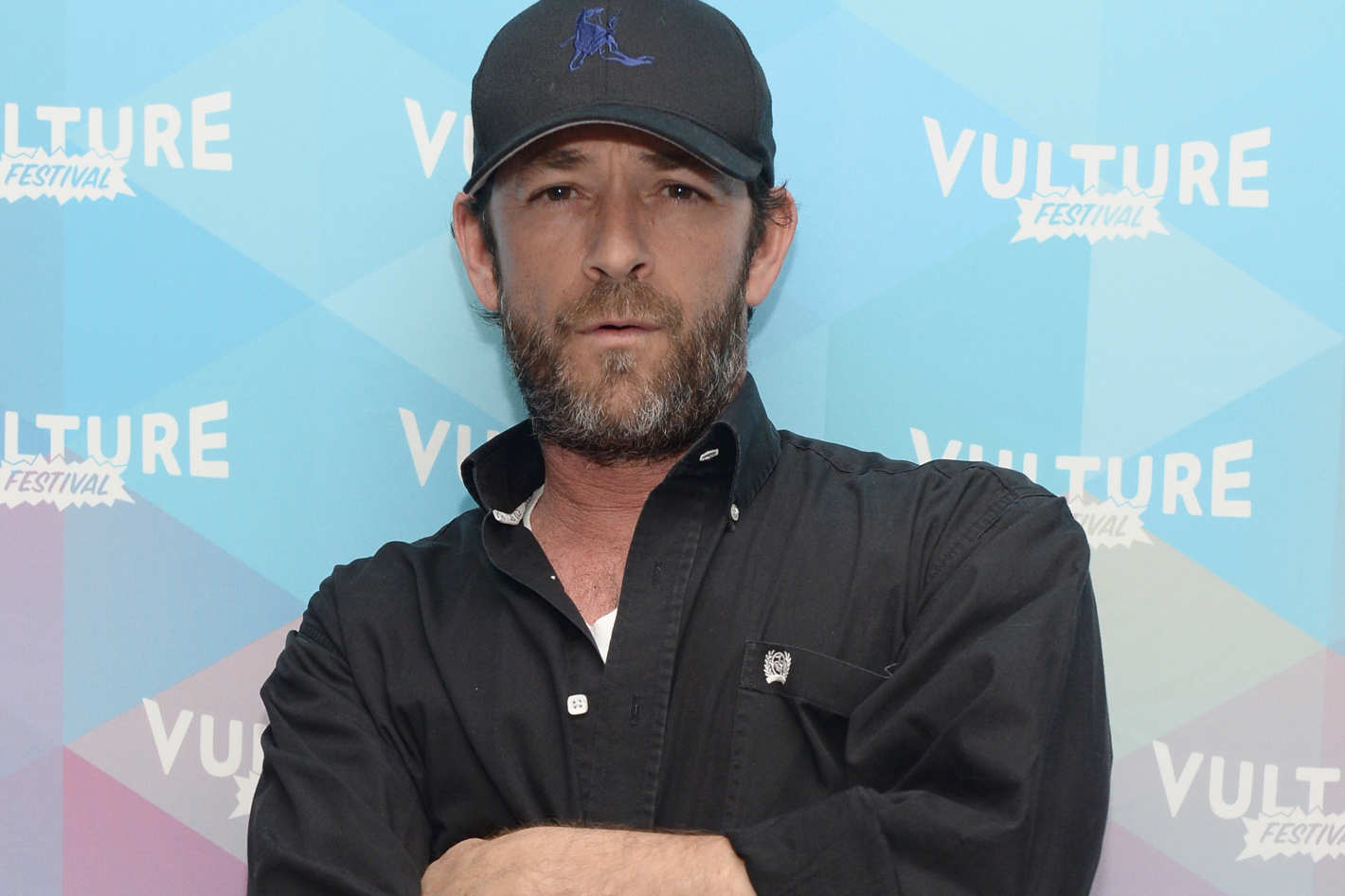 Luke Perry at a photoshoot. He is wearing a black shirt and a black golfing hat