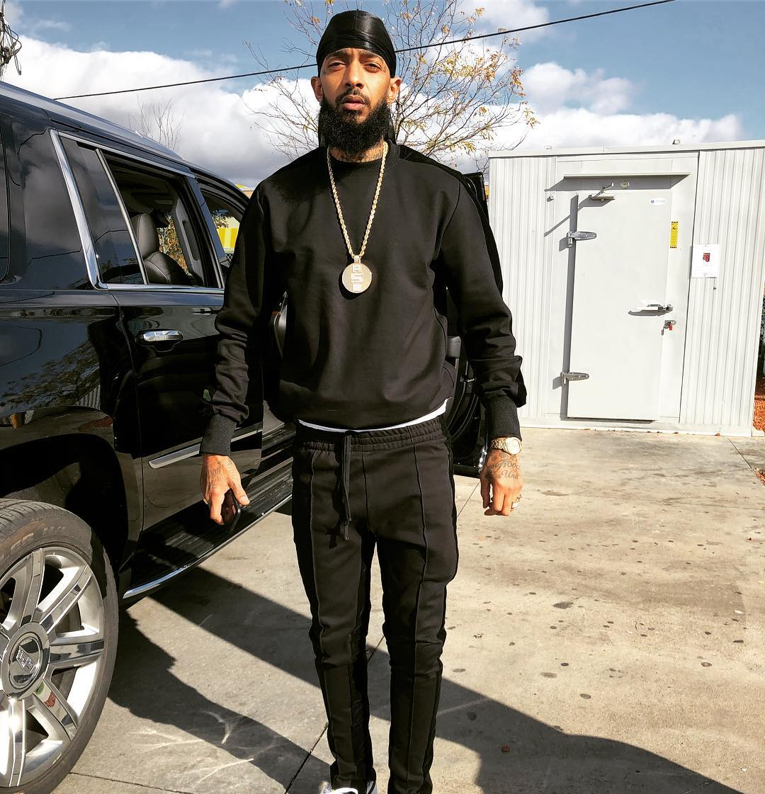 Nipsey Hussle wearing black attire and a do-rag