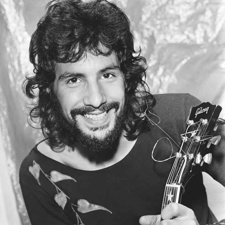 Black and white image of Cat Stevens with his guitar