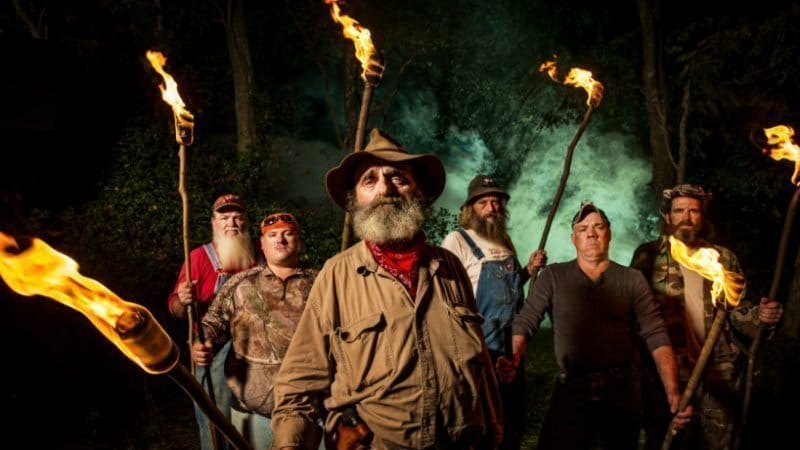 The cast members appear in a promo still, holding torches in the night