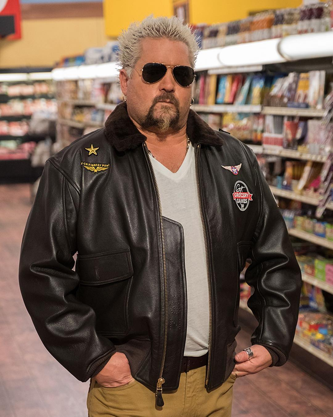 Guy Fieri at a store wearing a leather jacket and sun glass