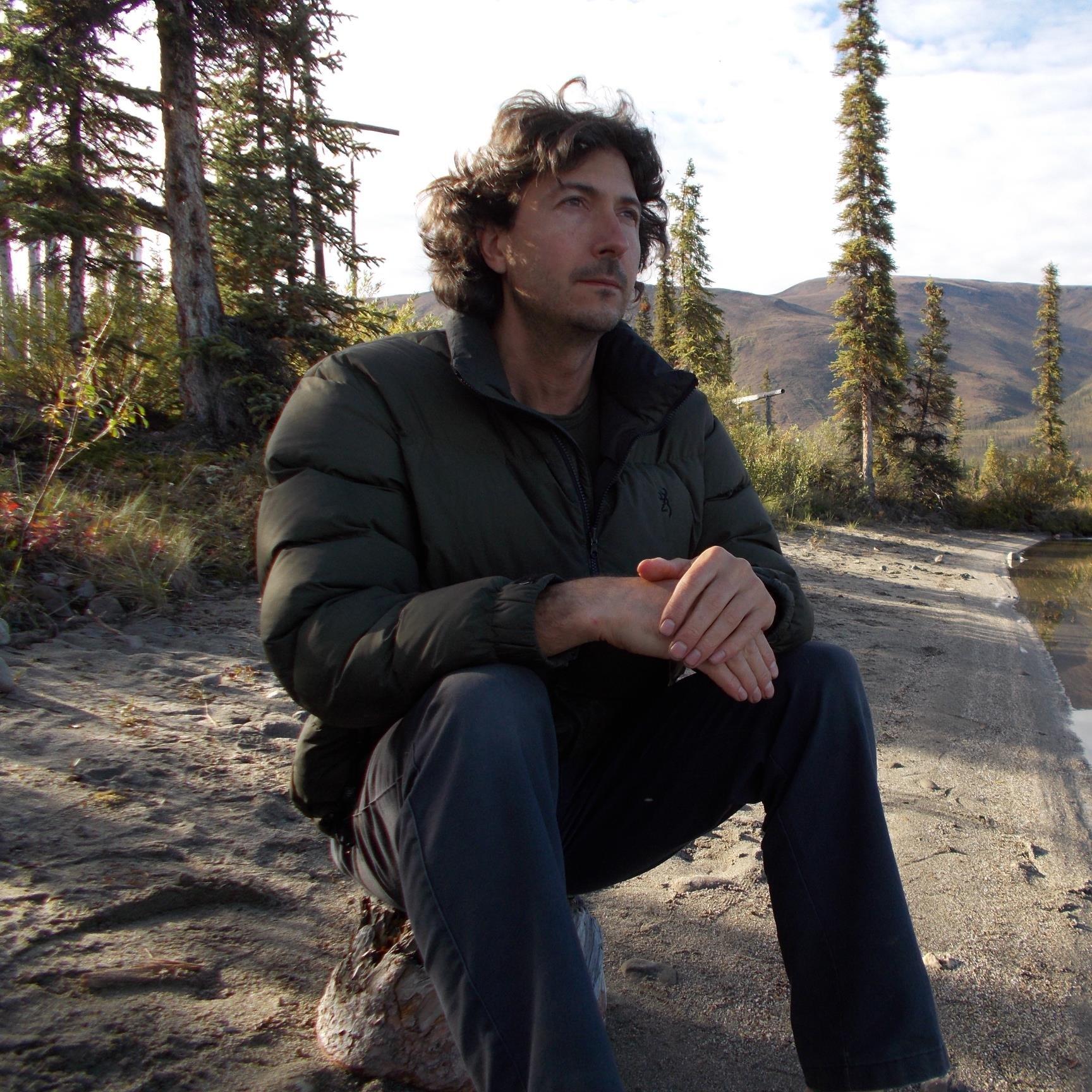 Glenn Villeneuve is sitting on a stone