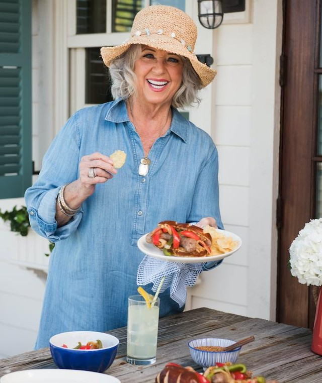 Paula Deen holding food in her one hand with a wide smile on her face