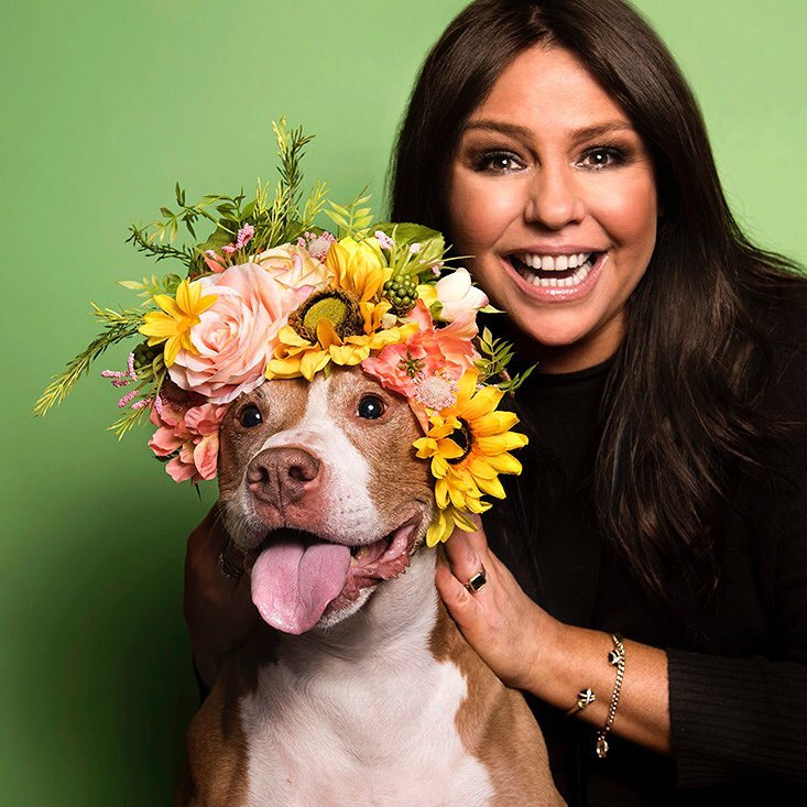 Rachael Ray is holding a dog, which is wearing a floral band on its head
