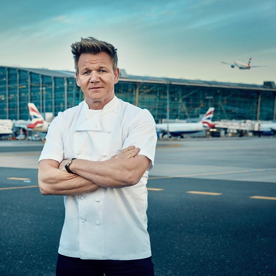 Gordon Ramsay in a white chef shirt while standing at airport with his arms folded