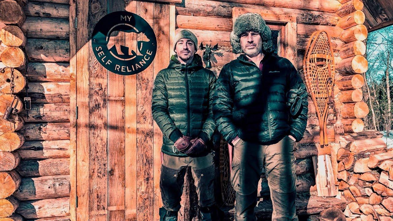 Glenn Villeneuve and Joe Robient standing infront of a log cabinet