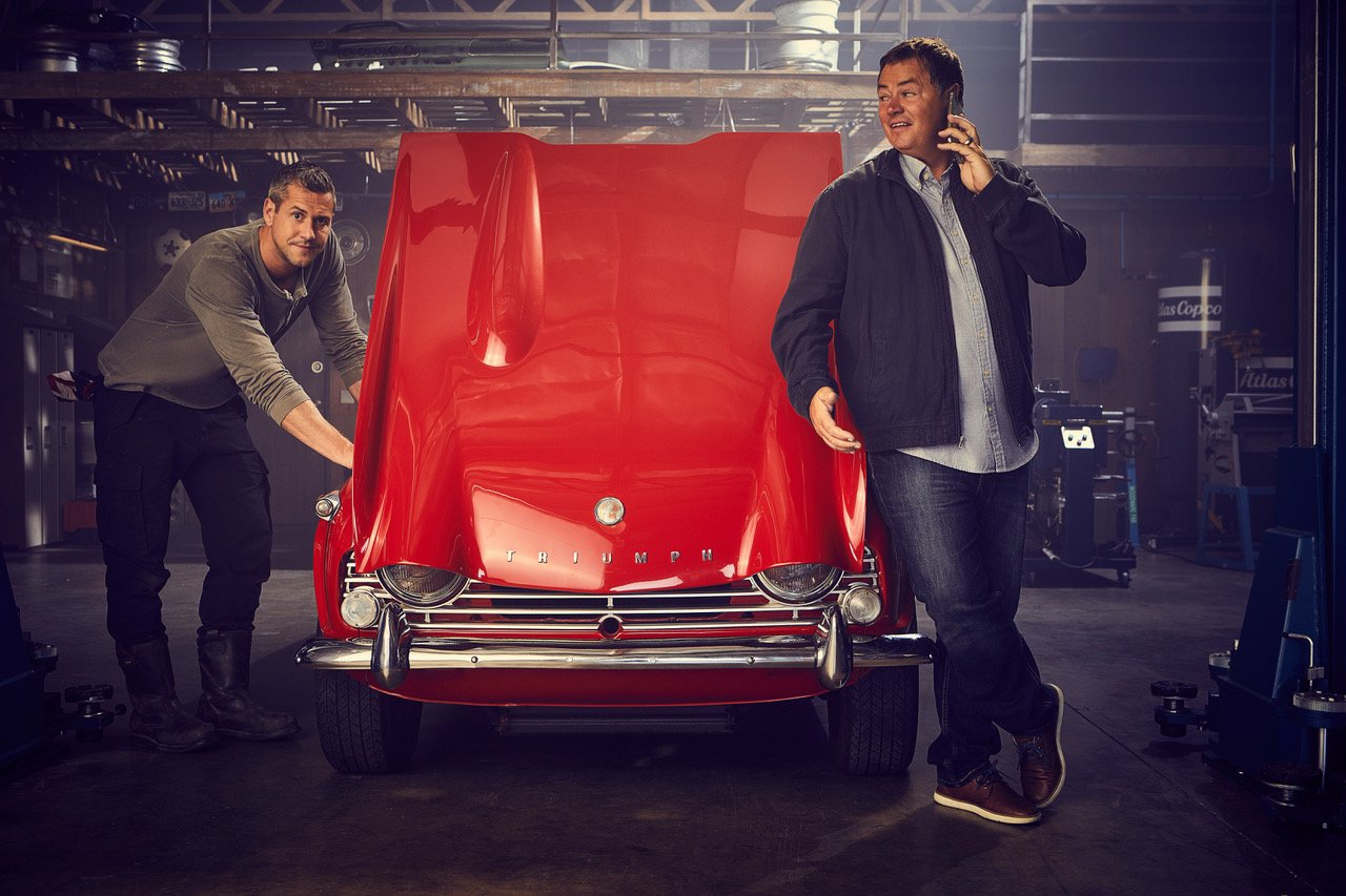 Ant and Mike in a promotional picture of Wheeler Dealers. Mike is standing infront of a red car like he is taking on a phone