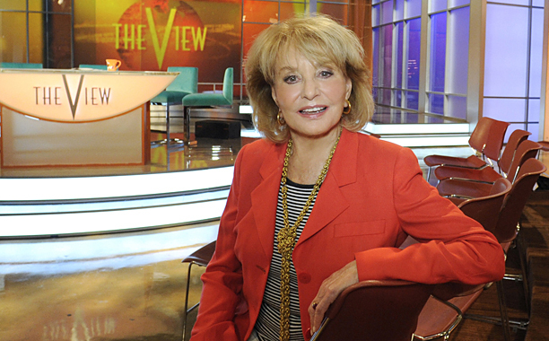 Barbara Walters on the set of The View. She is wearing a red coat and relaxing in between a production break