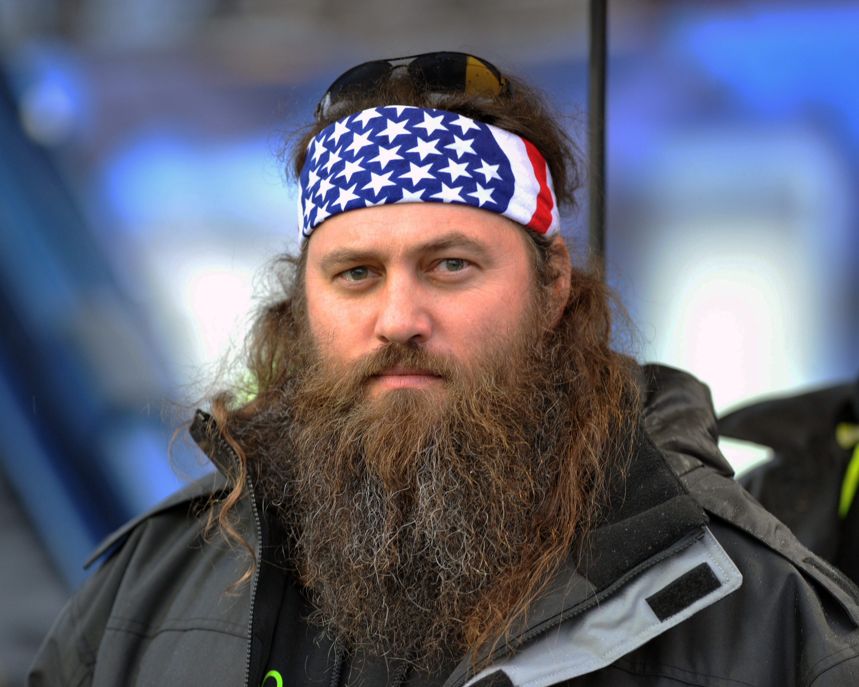 Willie is wearing a bandana with the American Flag painted on it. He has a bushy beard
