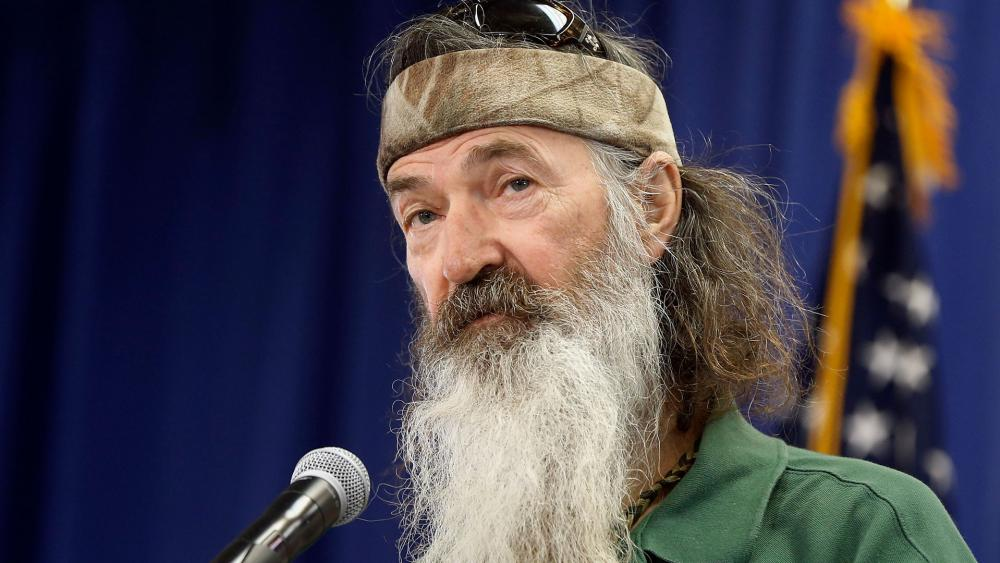 Phil speaks to a crowd at an event. He is wearing a grey bandana and has a grey beard
