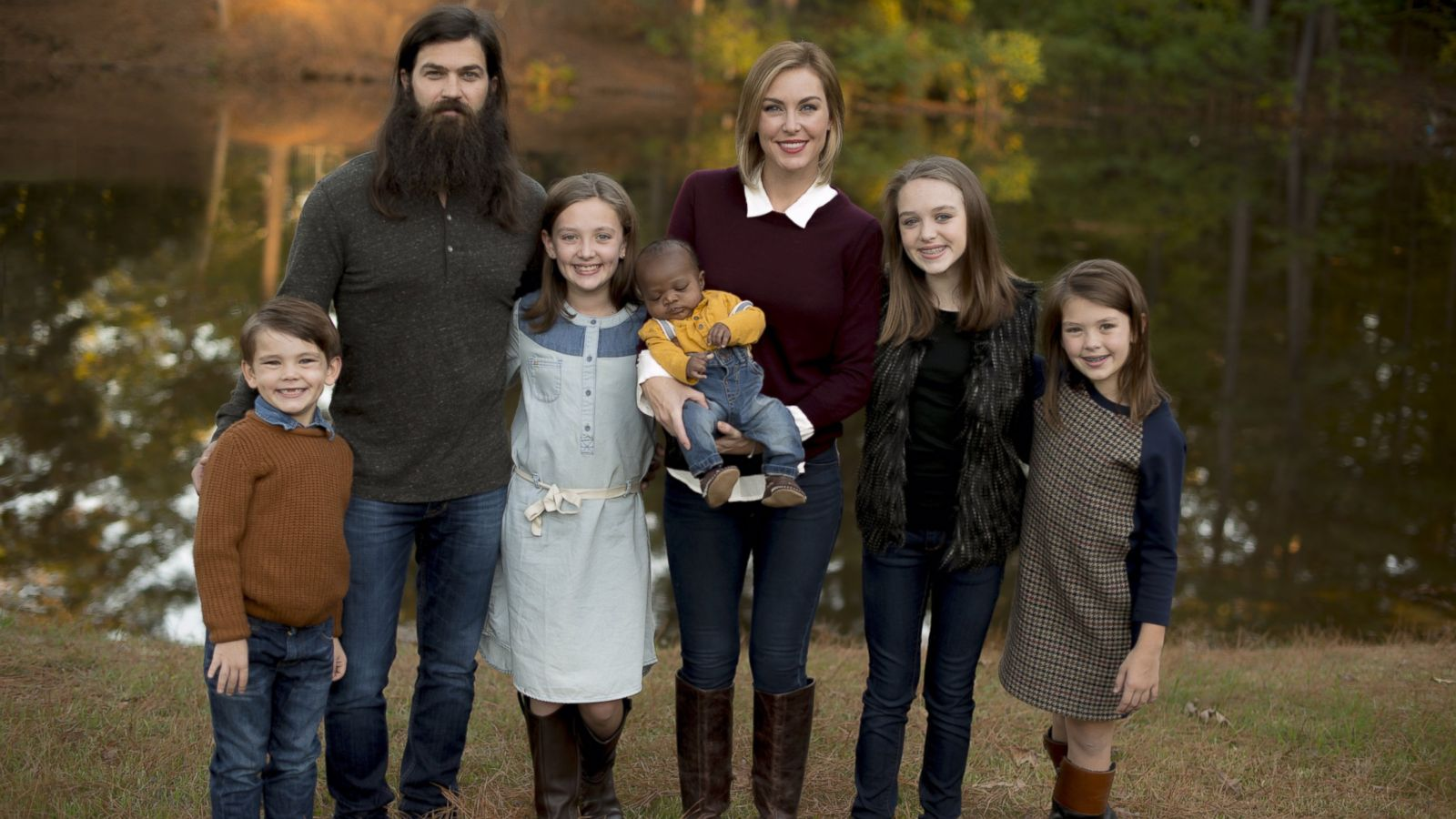 A family picture of Jep and Jessica. Their five children are present and they are standing in front of a lake