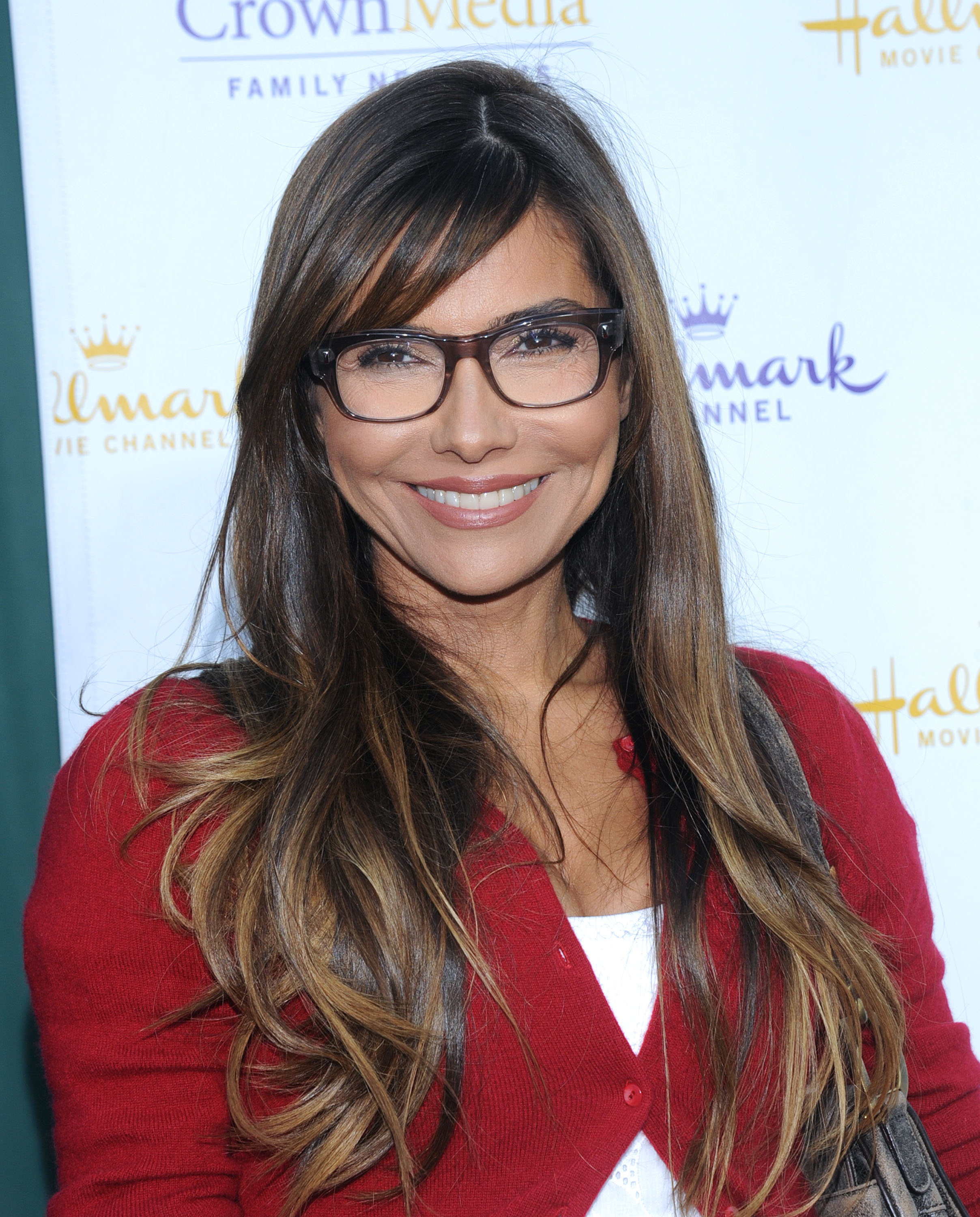 Vanessa Marcil smiling. She is wearing red shirt and and glasses