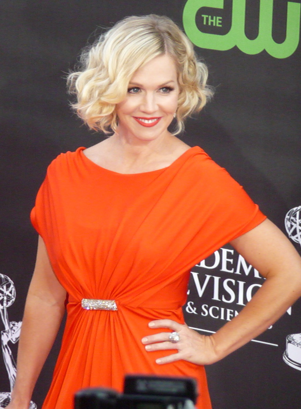 Jeannie Garth wearing a orange dress