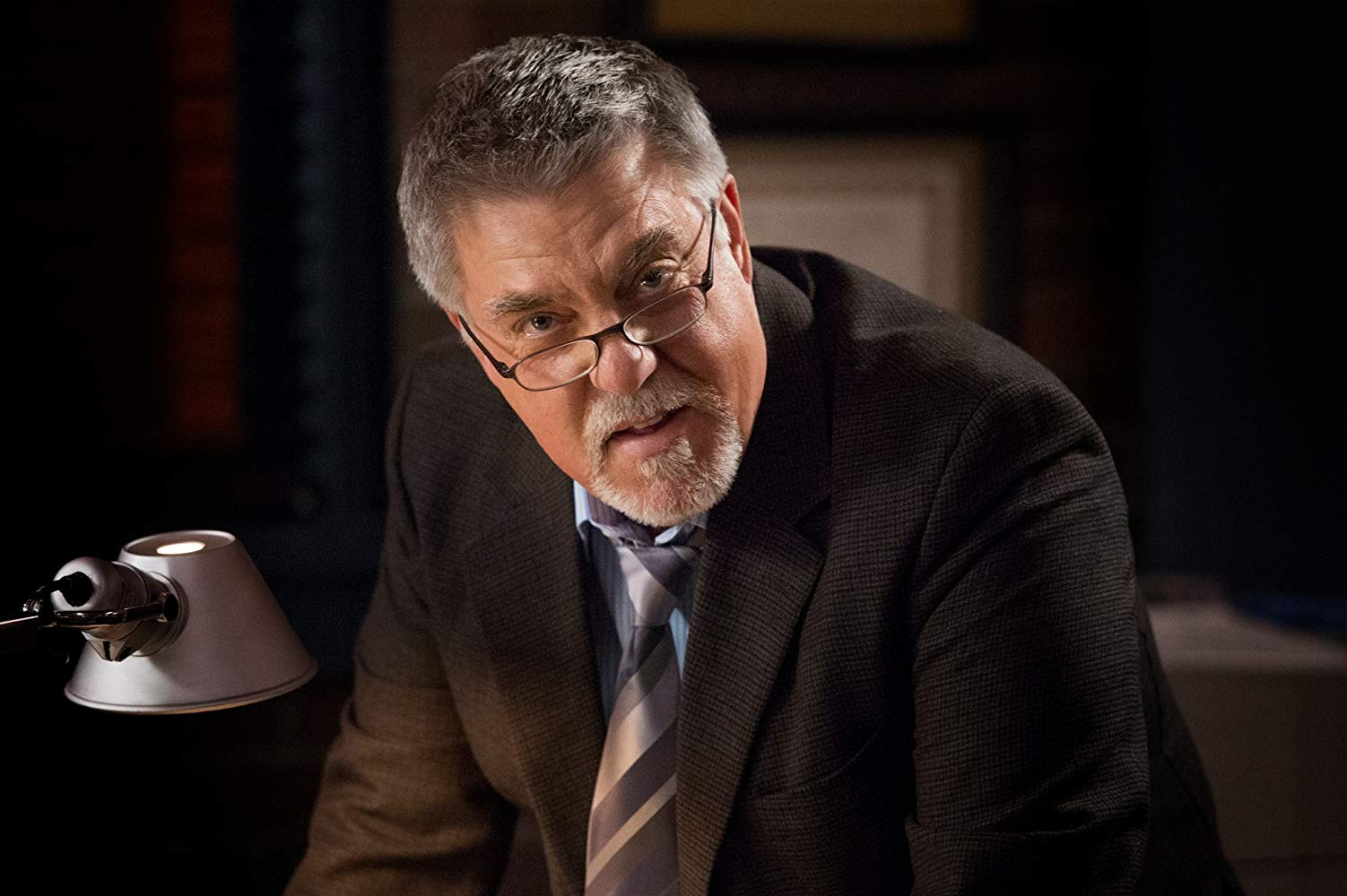A promo pic of McGill. He is wearing a brown suit and glasses as he looks at the camera