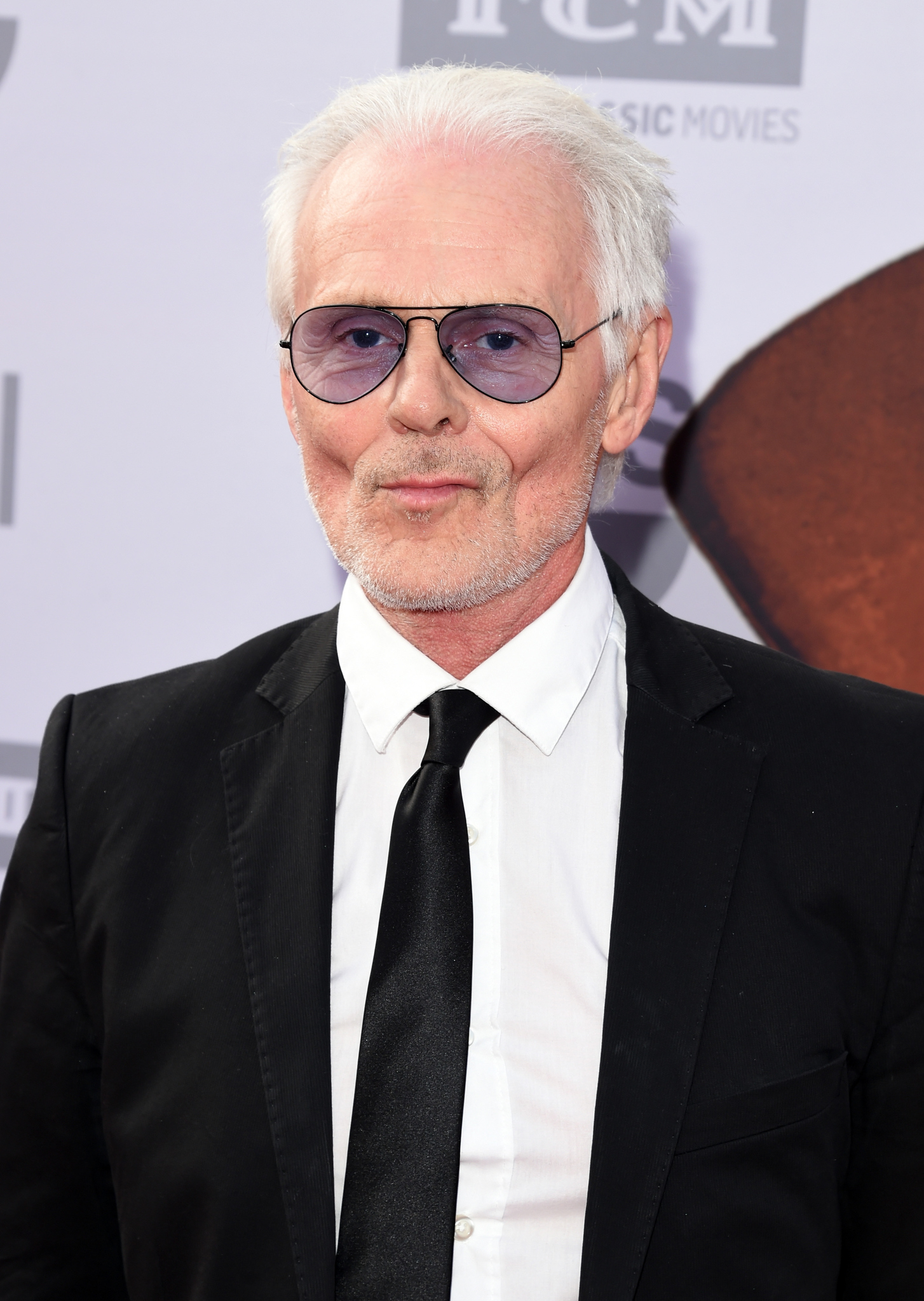 A recent picture of actor and singer Michael Des Barres at a red carpet event. He is wearing a sleek black suit and transparent blue lens shades