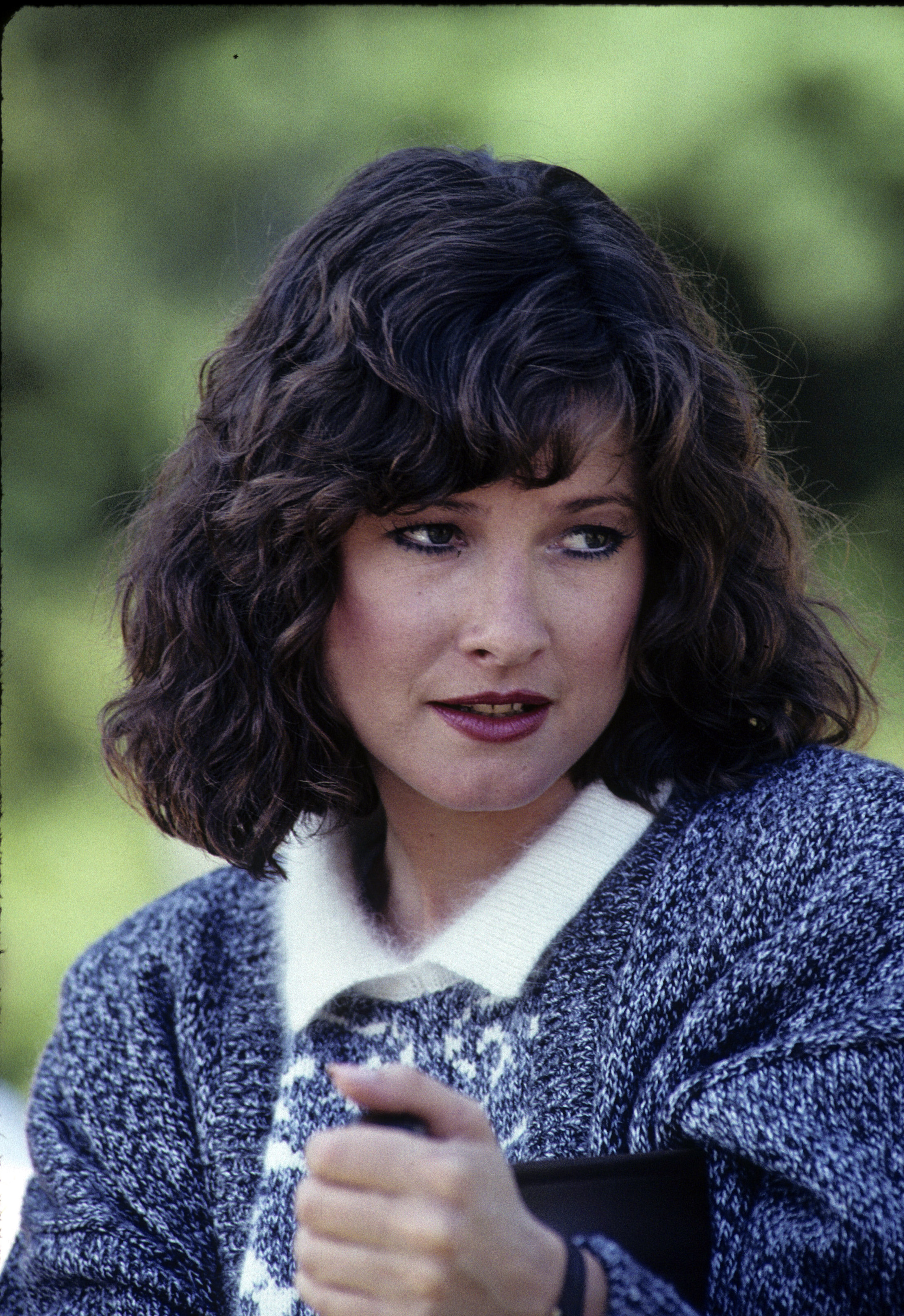 A picture of Elyssa Davalos in her youth. She is wearing a grey coat and has short, wavy hair