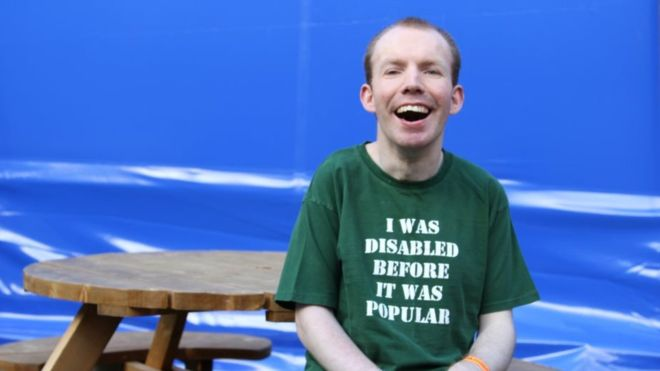 """Lee Ridley sitting on a wooden chair, wearing a green t-shirt which reads """"I WAS DISABLES BEFORE IT WAS POPULAR"""""""