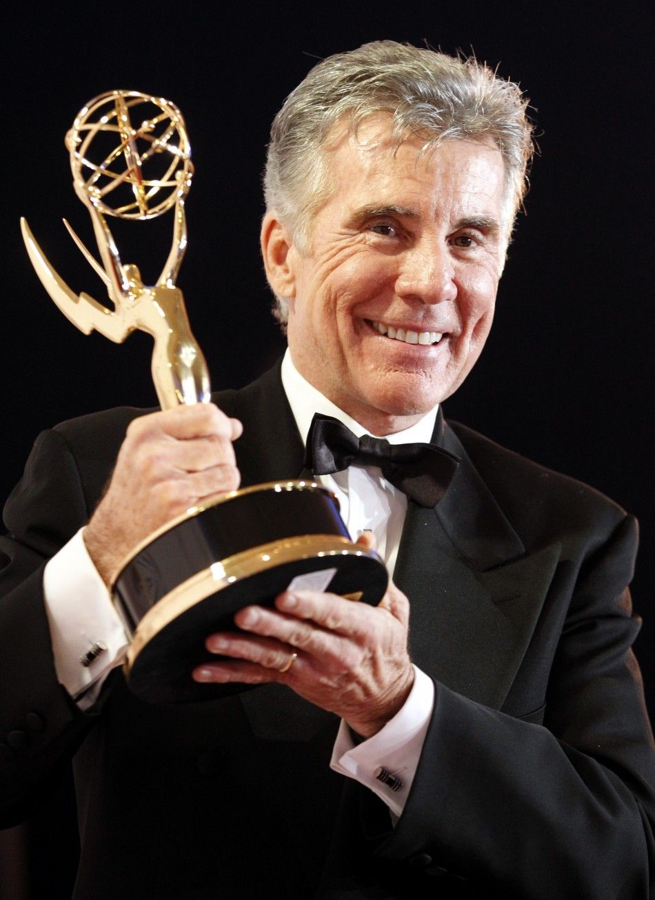 John Walsh looking happy holding his emmy award wearing a black suit
