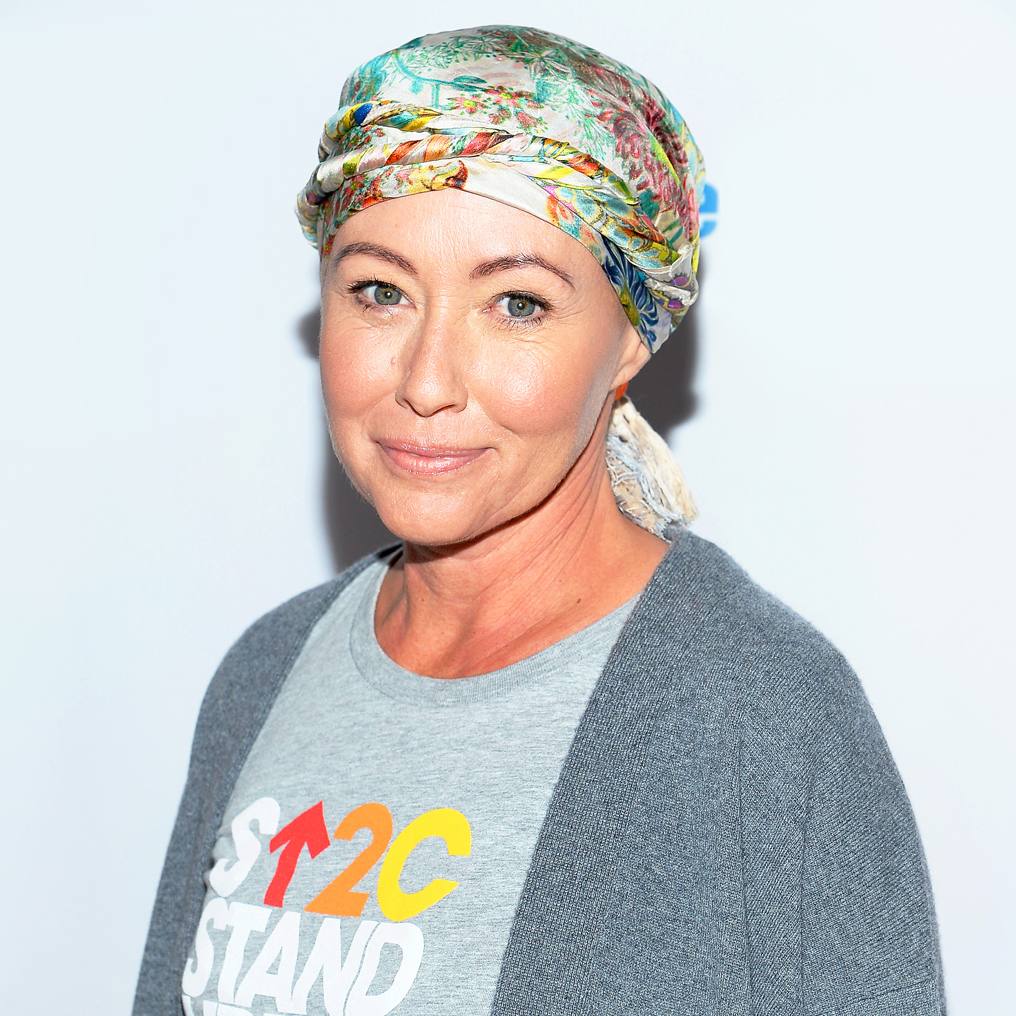 Shannen Doherty smiling. She has wrapped a scarf around her head