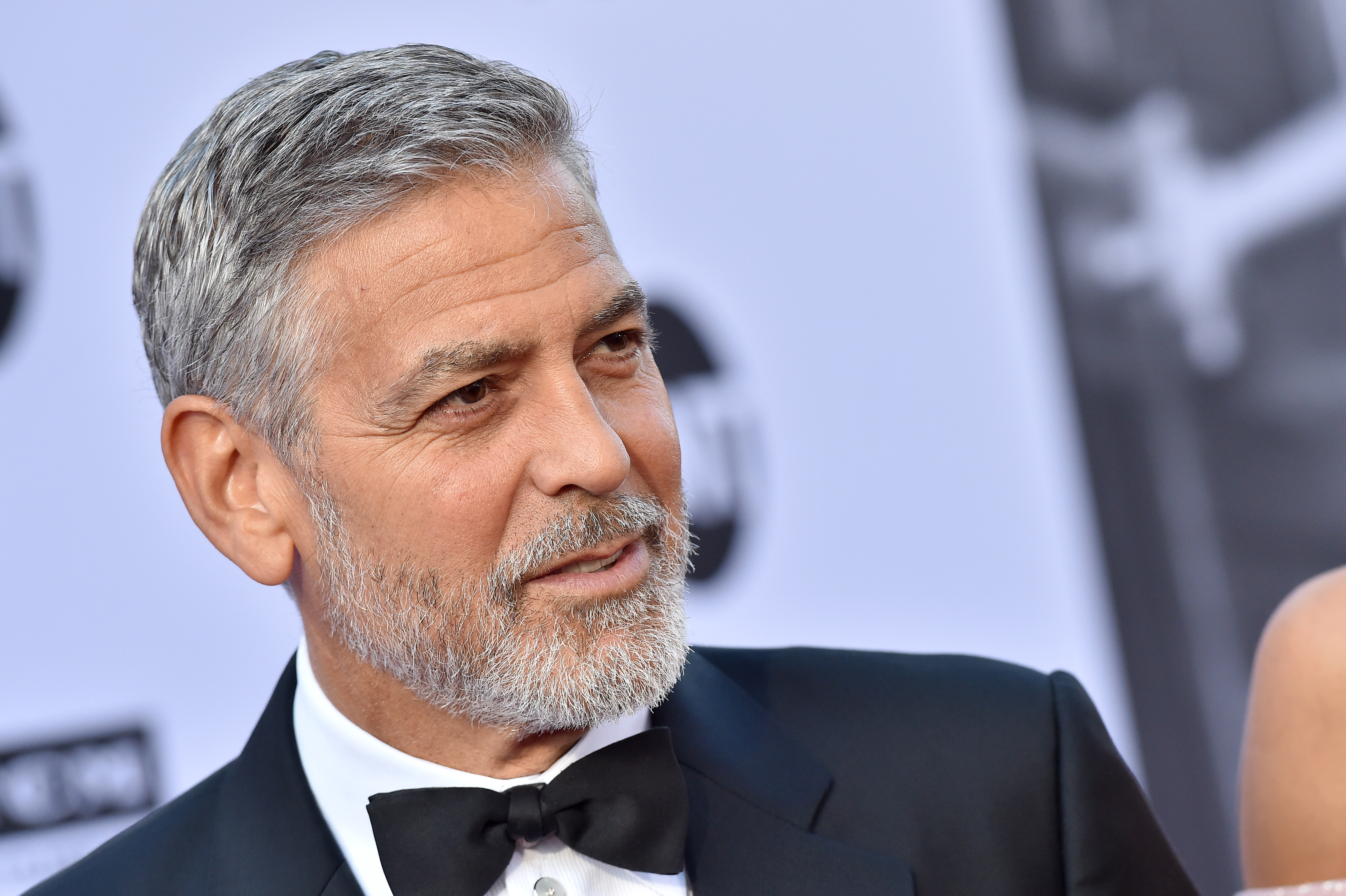 George Clooney posing for a pictur at premiere, wearing a suit with a bow tie
