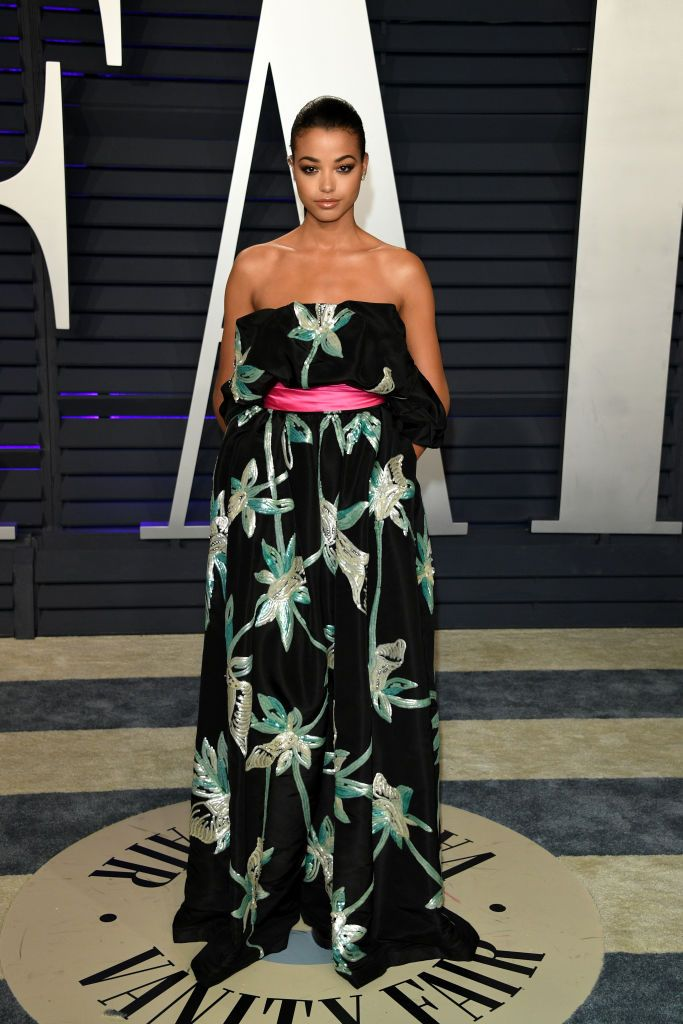 Ella Balinska at Vanity Fair. She is wearing a black dress. She is the daughter of English chef/former model, Lorraine Pascale and a Polish entrepreneur/musician, Kaz Balinski-Jundzilł.