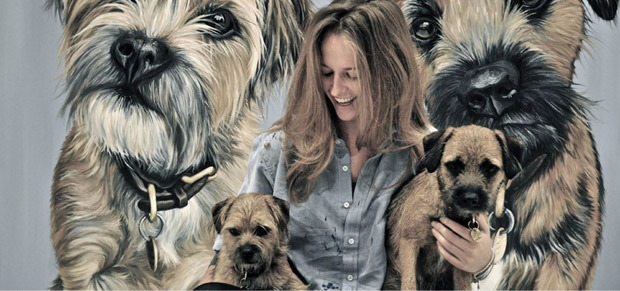 Kim Sears is holding her dogs and in the background is her portrait