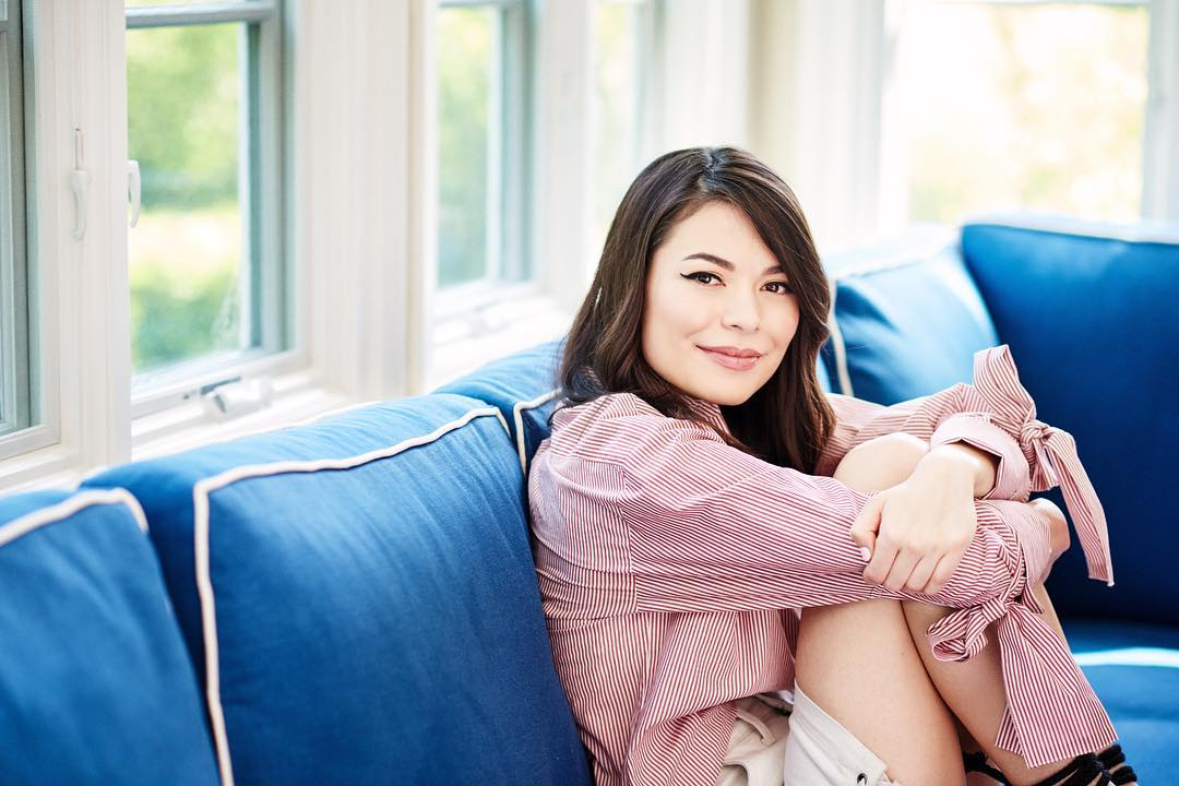 Miranda Cosgrove is sitting in a blue couch and has her arms around her knee