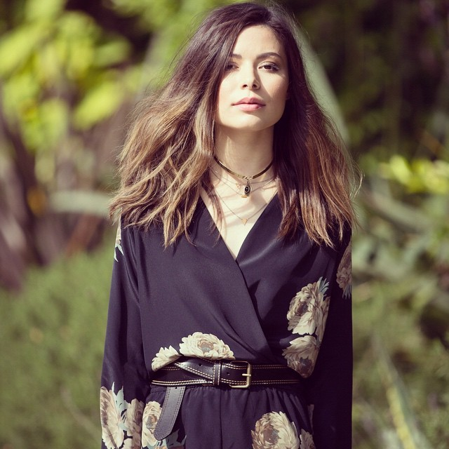 Miranda Cosgrove has let her hair loose and is wearing a blue dress
