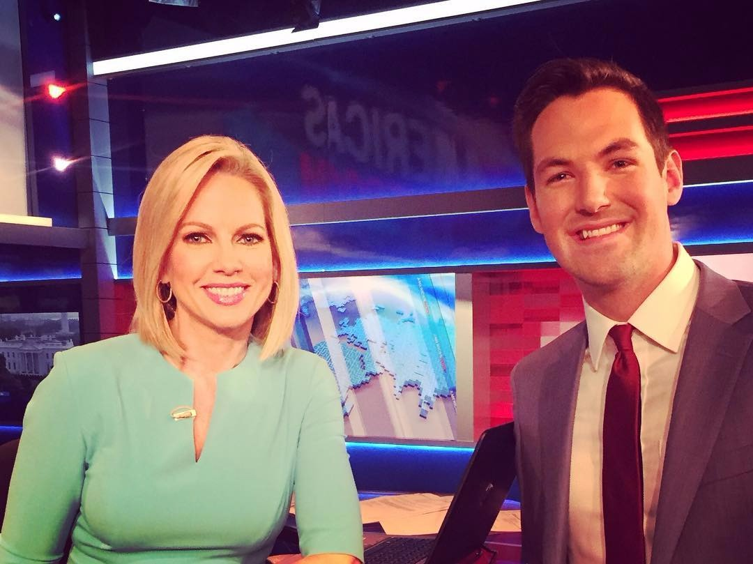 Shannon Bream poses with her co-host, Bill Hemmer. They both are smiling.