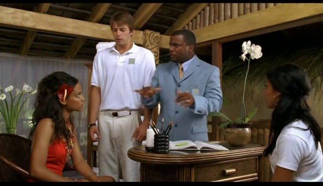 A scene captured from the movie Love Wrecked where Alfonso is trying to explain his guests about the resort he is working at.