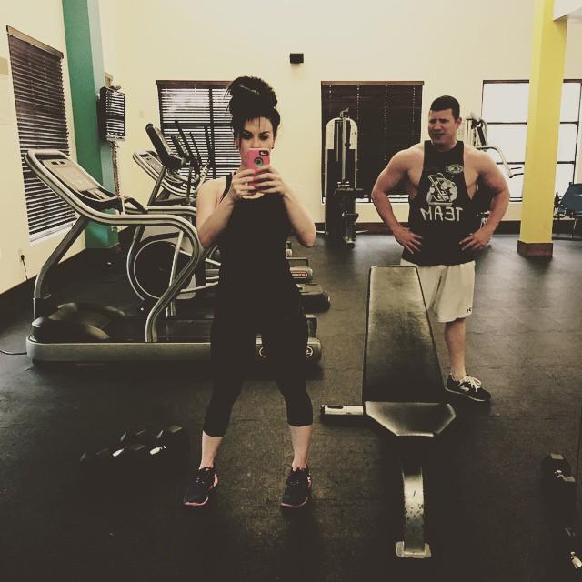 Jennifer Brenna taking a mirror selfie in the gym